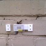 Маяк установленный на трещине в кирпичной стене